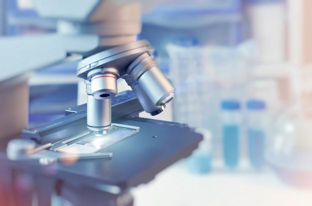 Científico com closeup no microscópio de luz e laboratório turva Foto Premium