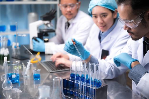 Cientista asiático segurar um tubo de ensaio cheio de líquido no laboratório Foto Premium