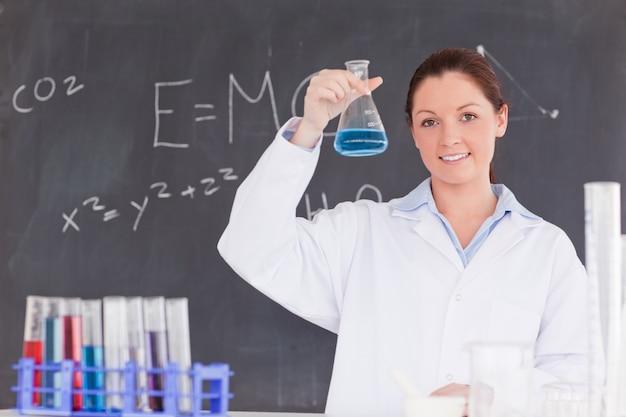 Cientista bonito que mostra um recipiente preenchido com um líquido azul Foto Premium