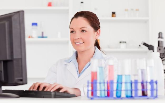 Cientista de cabelos vermelhos digitando um relatório com o computador Foto Premium