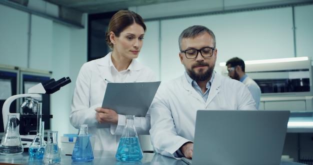 Cientista de homem caucasiano no manto branco e óculos trabalhando no computador portátil durante algumas pesquisas enquanto sua colega vem com alguns documentos ou resultados e pergunta algo Foto Premium