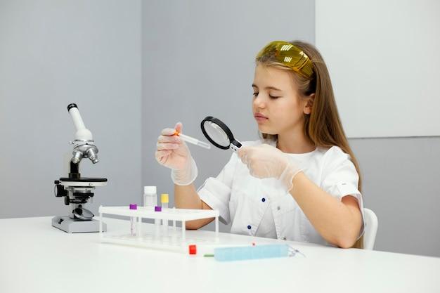 Cientista garota com óculos de segurança e microscópio Foto gratuita