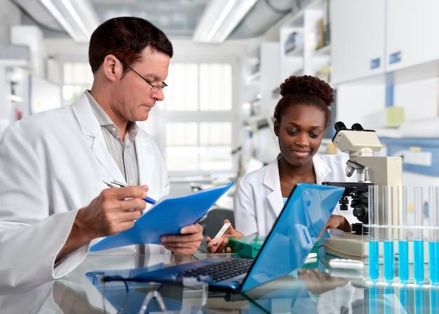 Cientistas, homem caucasiano e mulher africana, trabalham em laboratório Foto Premium