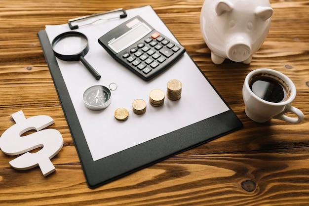 Cifrão; chá preto e piggybank com prancheta no plano de fundo texturizado de madeira Foto gratuita