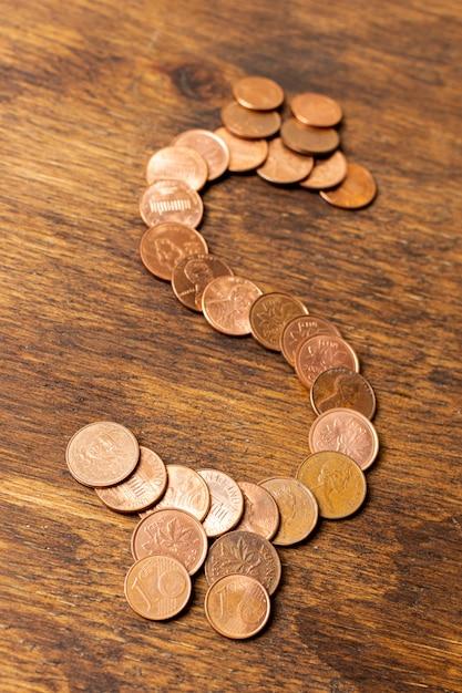 Cifrão feito de moedas no fundo de madeira Foto gratuita
