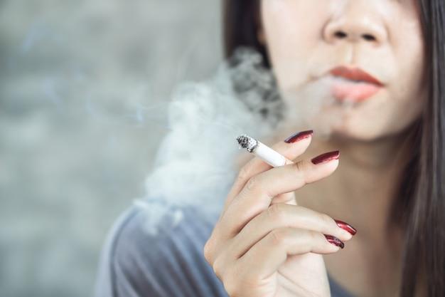 Cigarro de fumo de mão de mulher asiática Foto Premium