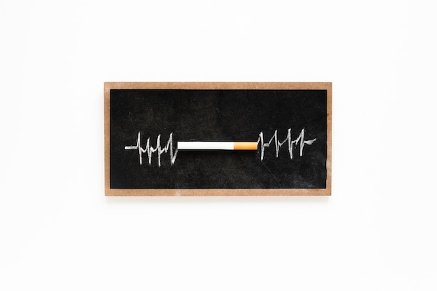 Cigarro de vista superior num quadro-negro Foto gratuita