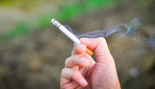 Cigarro na mão / fumaça de cigarro queimando na mão homem fumando no fundo ao ar livre Foto Premium