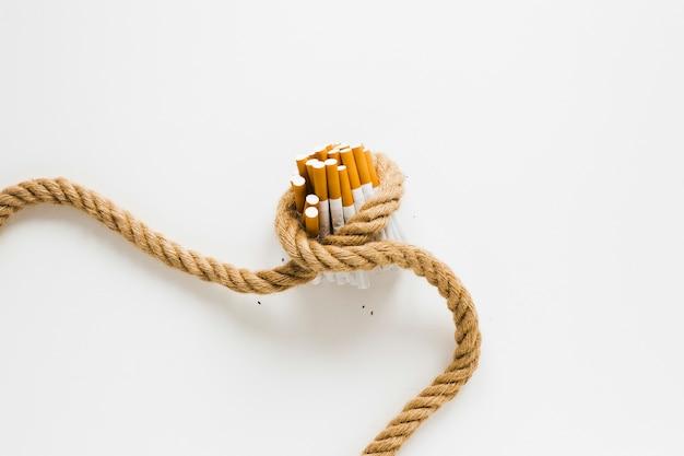 Cigarros de vista superior amarrados por uma corda Foto gratuita