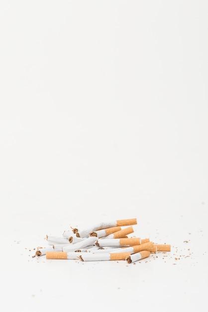 Cigarros quebrados em fundo branco, com espaço de cópia para escrever texto Foto gratuita