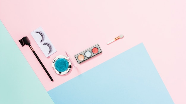Cílios artificiais; paleta de sombra e pincel de maquiagem em triplo fundo colorido Foto gratuita