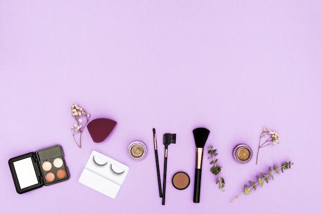 Cílios artificiais; paleta de sombras; liquidificador; pó compacto e pincéis de maquiagem com galho e gypsophila no fundo roxo Foto gratuita