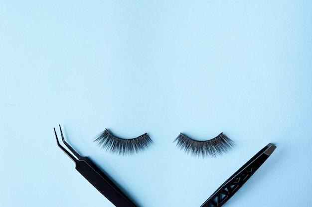 Cílios postiços com duas pinças pretas sobre fundo azul, com espaço de cópia Foto Premium