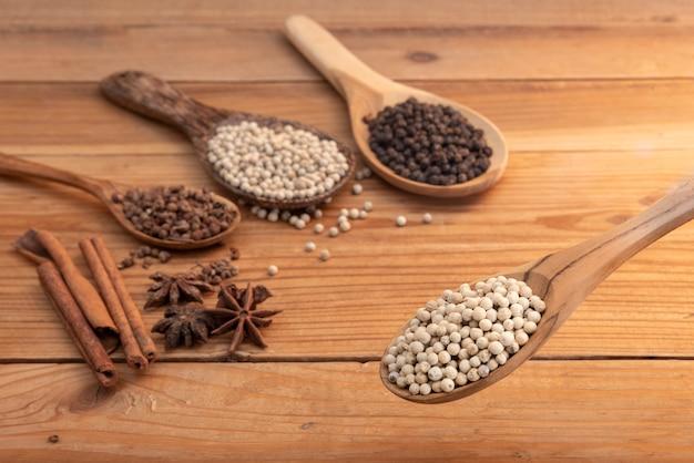 Cima, branca, pimenta, em, colher madeira, surround, com, tempero, pó, ligado, tabela madeira Foto Premium