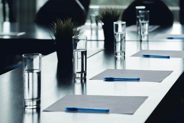 Cima, de, escuro, conferência, tabela, água, copos, canetas, folhas papel Foto Premium