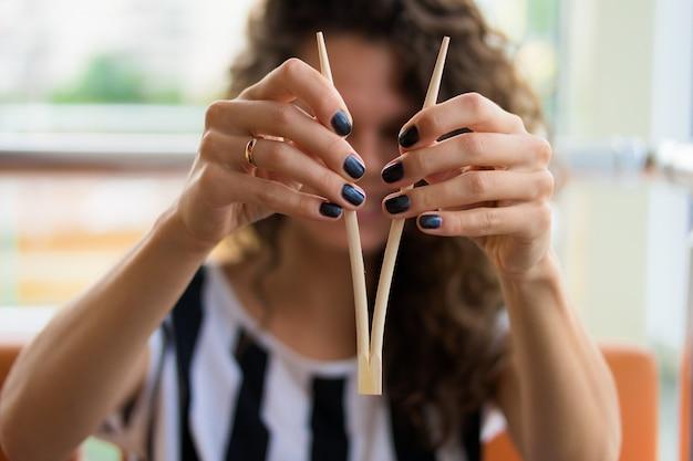 Cima, de, femininas, mãos manicure, segurando, a, chopsticks, para, sushi Foto Premium
