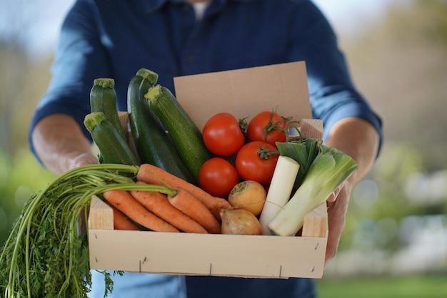 Cima, de, local, agricultor, segurando, crate, de, orgânica, sazonal, legumes, com, sinal Foto Premium