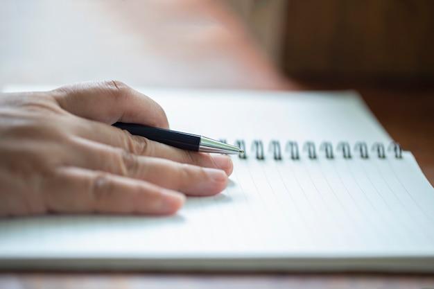 Cima, de, mão masculina, com, caneta, escrita, ligado, caderno, ligado, tabela madeira Foto Premium