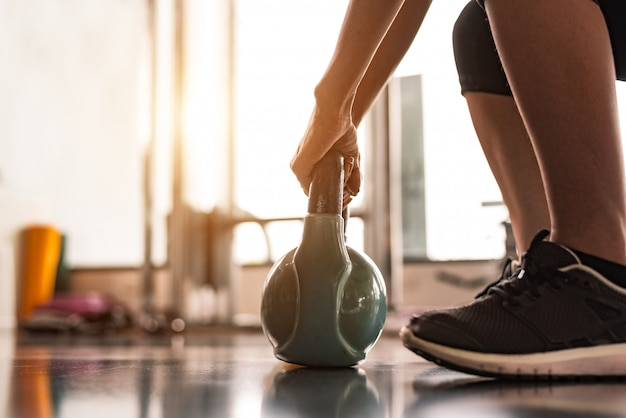 Cima, de, mulher, levantamento, kettlebell, semelhante, dumbbells, em, condicão física, desporto, clube, ginásio, treinamento Foto Premium