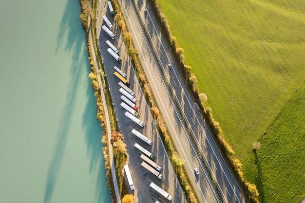 Cima para baixo a vista aérea da estrada interestadual com tráfego em movimento rápido e estacionamento com caminhões estacionados. Foto Premium
