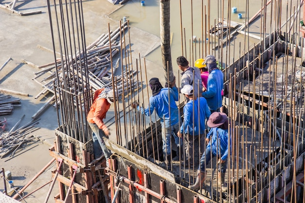 Cimento de derramamento do trabalhador que derrama em fundações e na área do molde das colunas no canteiro de obras. Foto Premium