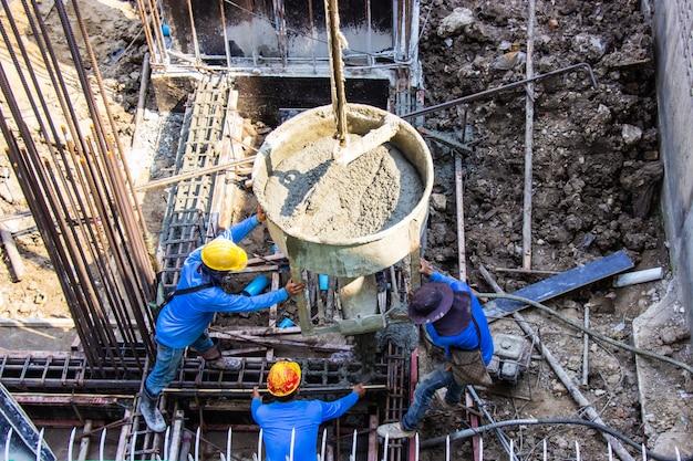 Cimento de derramamento do trabalhador que derrama no molde das fundações na área de construção no canteiro de obras. Foto Premium