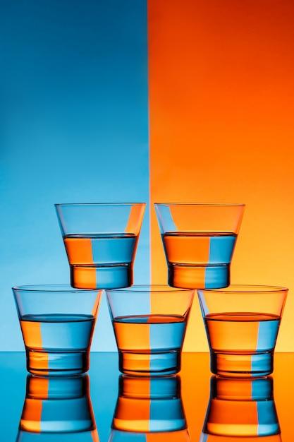 Cinco copos com água sobre o fundo azul e laranja. Foto gratuita