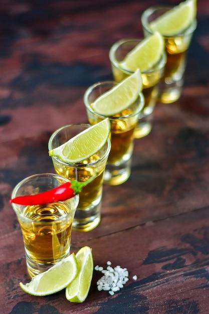 Cinco doses de tequila com salgadinhos de limão e pistache, sal e pimenta para decoração, vodka, uísque, rum Foto Premium
