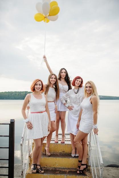 Cinco mulheres com balões à mão weared em vestidos brancos na festa da galinha contra o cais no lago. Foto Premium