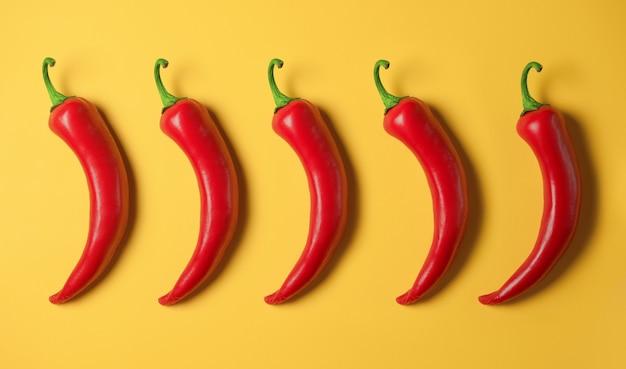 Cinco pimentas vermelhas em um amarelo Foto Premium