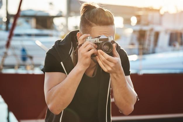Cinegrafista tentando segurar ainda para não assustar os pássaros. retrato do fotógrafo masculino jovem focado, olhando através da câmera e franzindo a testa, sendo focado no modelo durante a sessão de fotos perto da beira-mar no porto Foto gratuita