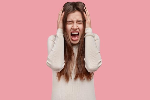 Cintura para cima, foto de uma mulher europeia desesperada e estressante grita de aborrecimento, fica louca e fica de queixo caído Foto gratuita