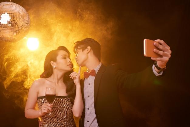 Cintura para cima tiro de casal em roupas extravagantes, dando um beijo para selfie em uma festa Foto gratuita