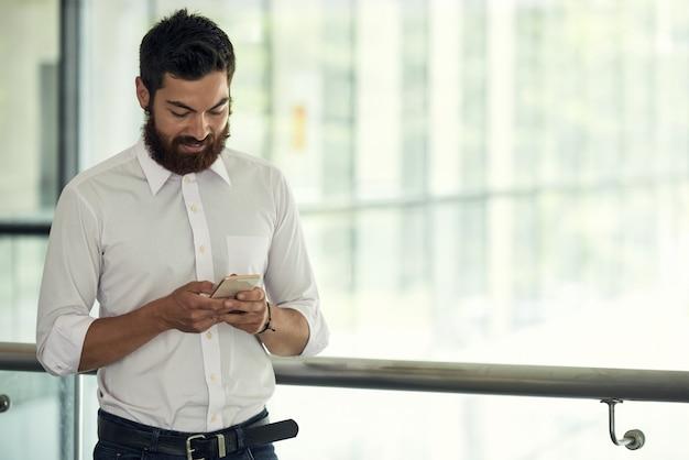 Cintura para cima tiro de homem de negócios na camisa branca usando seu smartphone em uma pausa Foto gratuita