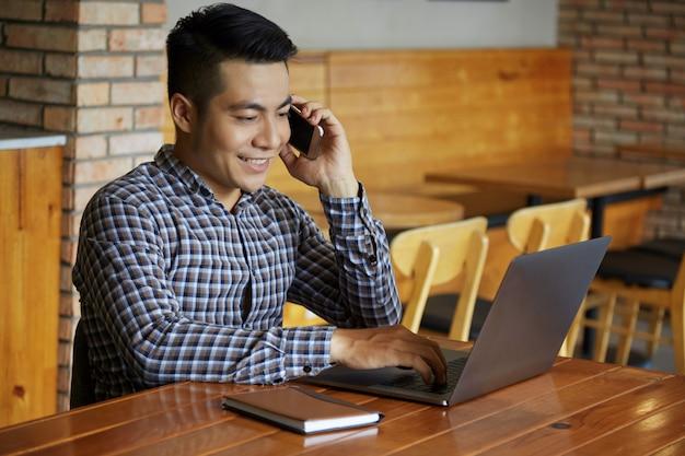 Cintura para cima tiro de homem trabalhando no laptop enquanto fala ao telefone Foto gratuita