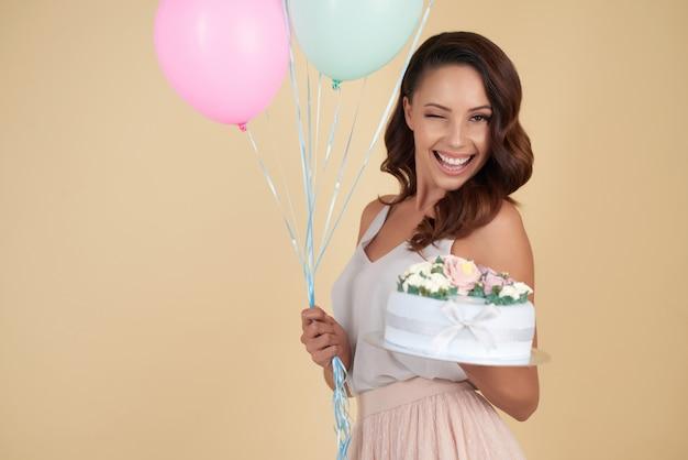 Cintura para cima tiro de mulher atraente com um bolo de aniversário e balões piscando para a câmera Foto gratuita