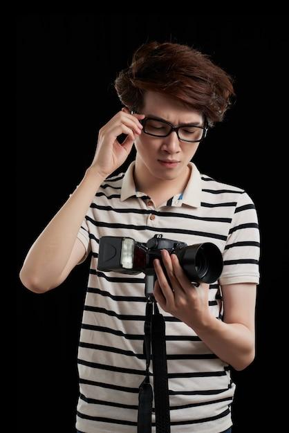 Cintura para cima tiro do fotógrafo asiático contra fundo preto, olhando para a câmera com expressão decepcionada do rosto Foto gratuita