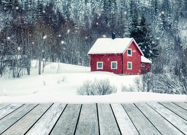 Cinza de madeira com casa vermelha em nevando no inverno | Foto Premium