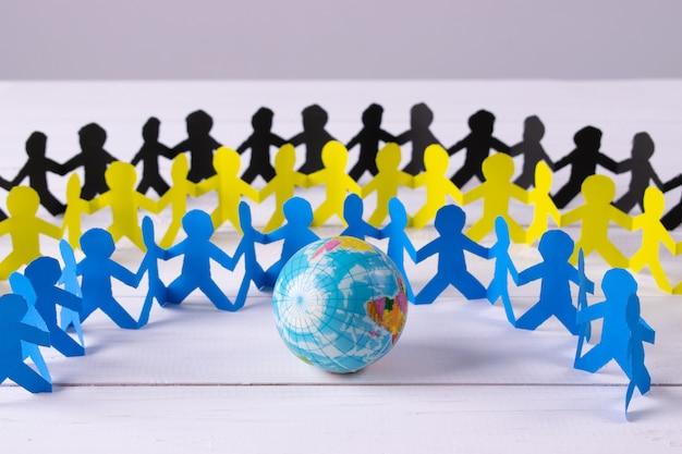 Círculo de pessoas de papel de mãos dadas ao redor do globo feito de papel cortado Foto Premium