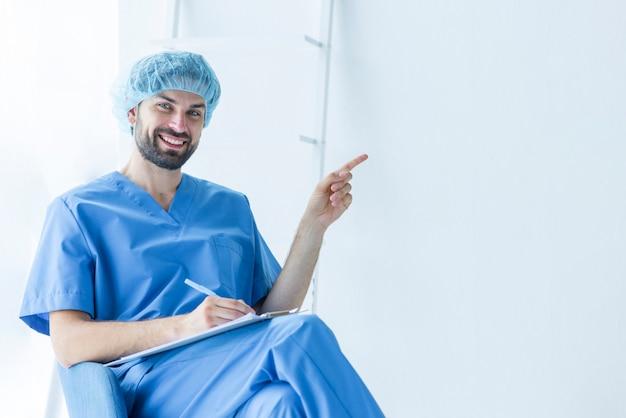 Cirurgião bonito com prancheta apontando para o espaço vazio Foto gratuita