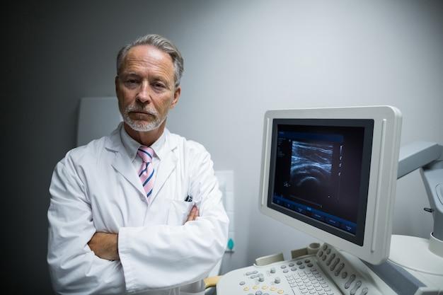 Cirurgião com os braços cruzados em pé perto da máquina do dispositivo ultrassônico Foto gratuita
