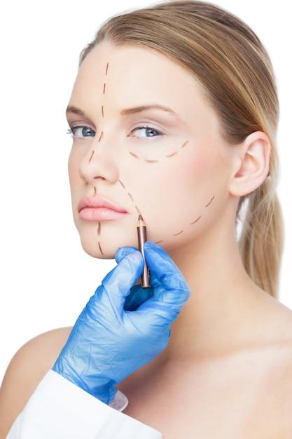 Cirurgião desenhando linhas pontilhadas sobre um paciente lindo Foto Premium