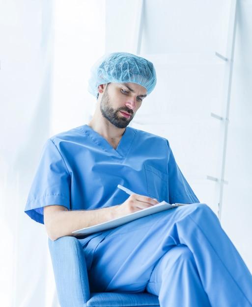 Cirurgião jovem fazendo anotações Foto gratuita
