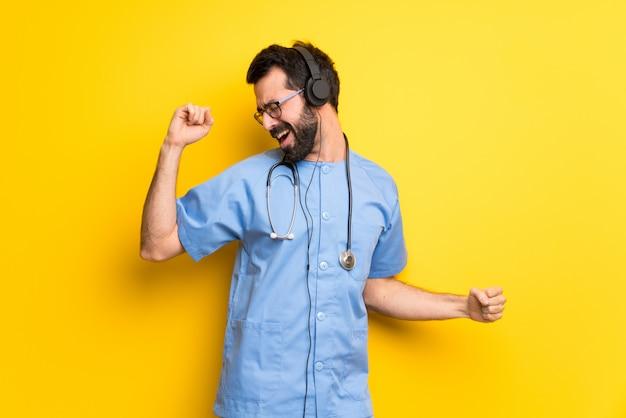 Cirurgião médico homem ouvindo música com fones de ouvido e dançar Foto Premium