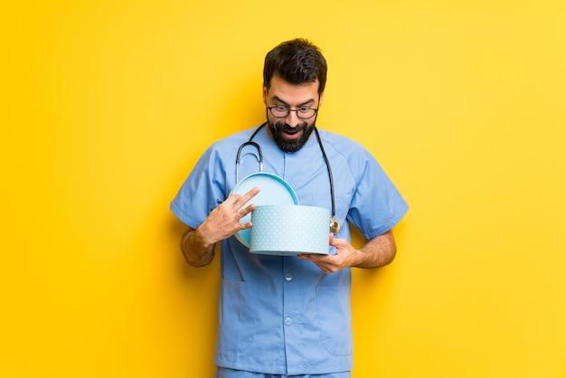 Cirurgião médico homem segurando um presente nas mãos Foto Premium