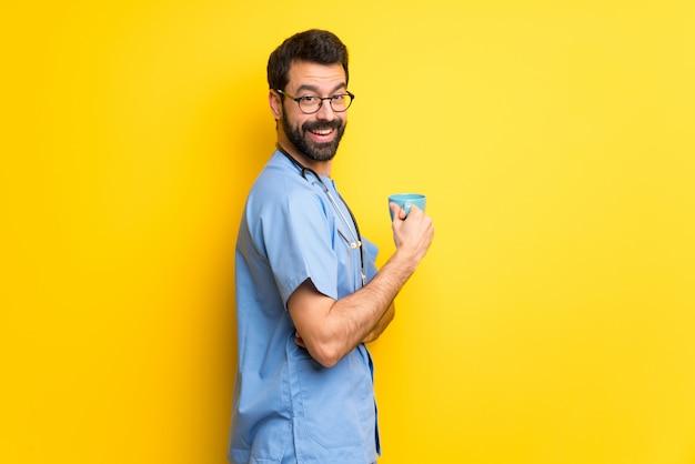 Cirurgião médico homem segurando uma xícara de café quente Foto Premium