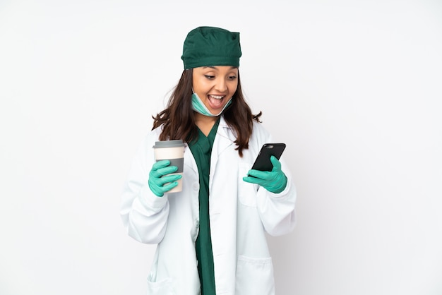 Cirurgião mulher de uniforme verde isolado na parede branca, segurando o café para levar e um celular Foto Premium