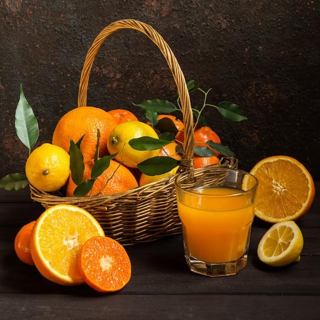 Citrinos de limão laranja em uma cesta e suco em um fundo escuro, dieta alimentar saudável Foto Premium
