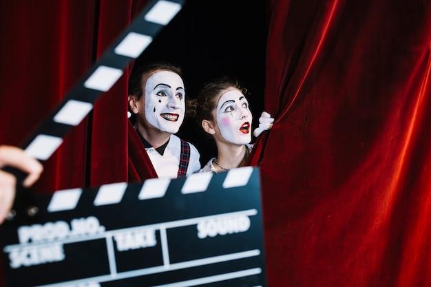 Clapperboard na frente do casal animado mime a espreitar por trás da cortina vermelha Foto gratuita