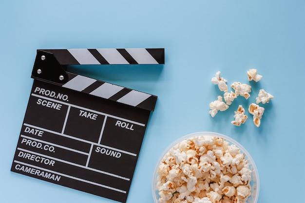 Claquete de cinema com pipoca em fundo azul para entretenimento Foto Premium